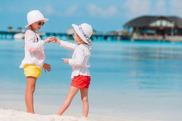 Очаровательные девчонки веселятся вместе на белом тропическом пляже