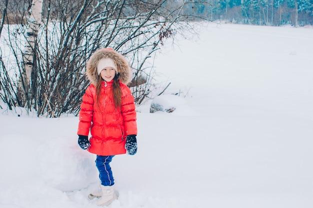 Портрет маленькой очаровательной девушки в снежный солнечный зимний день