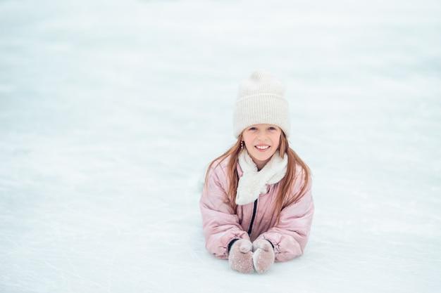 Маленькая прелестная девушка сидя на льде с коньками после падения