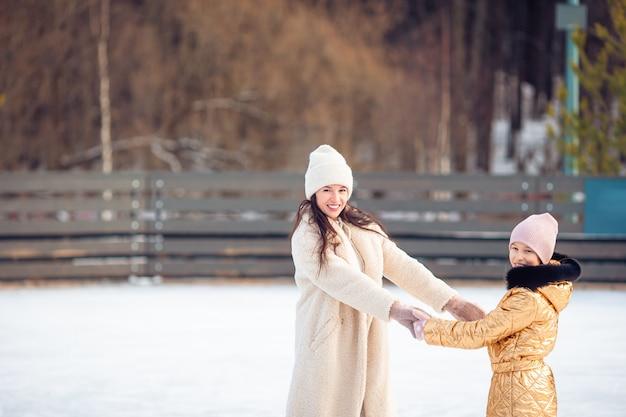 Маленькая прелестная девушка с матерью катается на катке