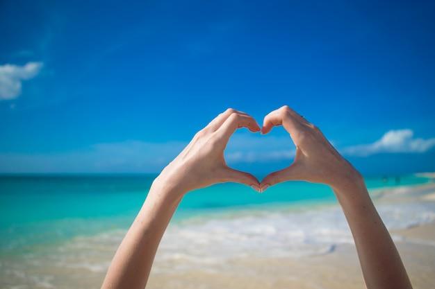 ターコイズブルーの海に女性の手によって作られた心のクローズアップ