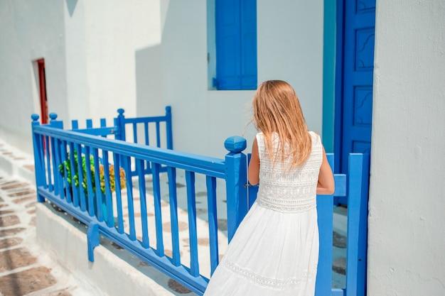 Очаровательная маленькая девочка на старой улице типичной греческой традиционной деревни