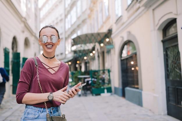街で彼女のスマートフォンを持つ女性