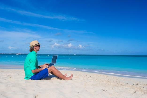 若い男が熱帯のビーチでのラップトップに取り組んで