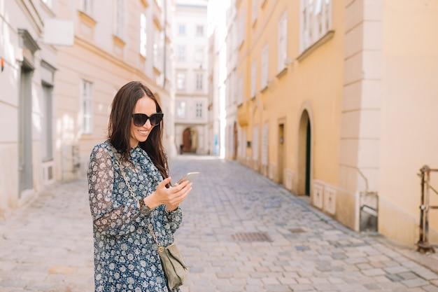 通りでスマートフォンを持つ女性