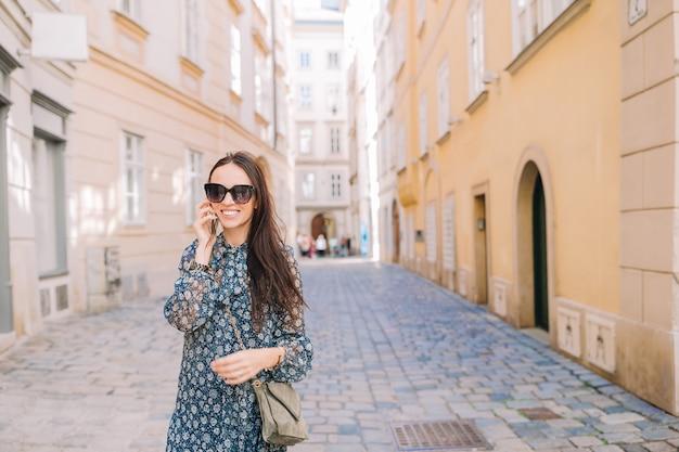 市内の彼女のスマートフォンで女性の話。イタリアの都市で屋外の若い魅力的な観光客