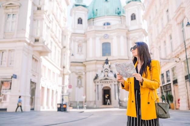Путешествие девушка с картой в вене на открытом воздухе во время каникул в европе.