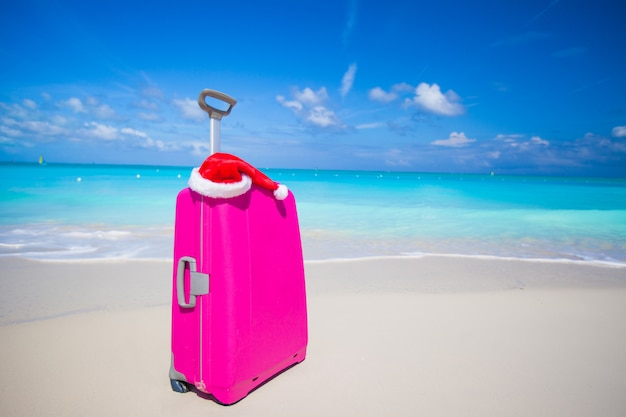 ピンクのスーツケースと白い砂のビーチでサンタクロースの帽子