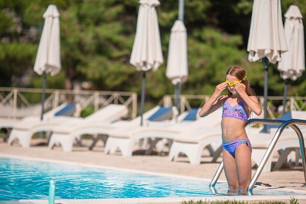 Маленькая прелестная девушка в открытом бассейне