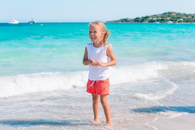 Прелестная маленькая девочка на пляже на летних каникулах