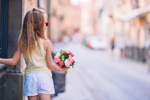花の花束が付いている通りのかわいい女の子