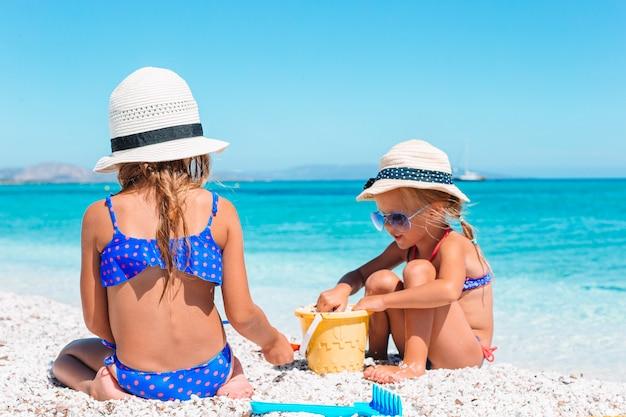 Две маленькие счастливые девочки играют с песком