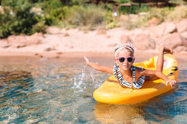 かわいい女の子は、透明な青緑色の水で黄色のカヤックで水泳を楽しむ