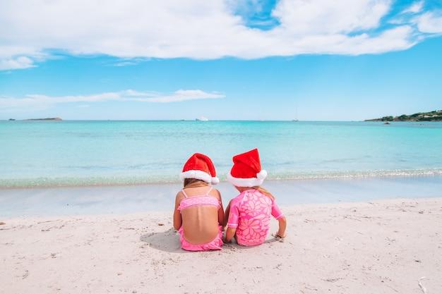 海岸に座っているサンタ帽子でかわいい女の子