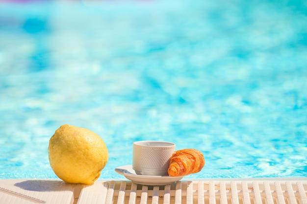 プールサイドでのレモン、コーヒー、クロワッサン