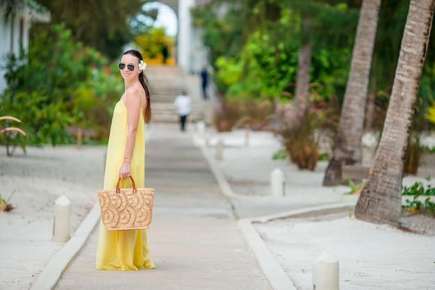 熱帯のビーチでの休暇中に帽子の若い女性。彼女の休日を楽しんで幸せな女の子の背面図