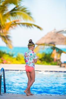 屋外スイミングプールで泳いでいるかわいい女の子