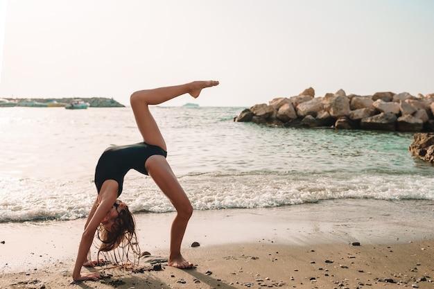 楽しい時を過すビーチでアクティブな女の子。海岸でスポーティな練習をするかわいい子供