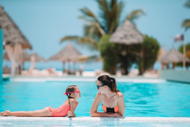 豪華なスイミングプールで夏休みを楽しんでいる家族