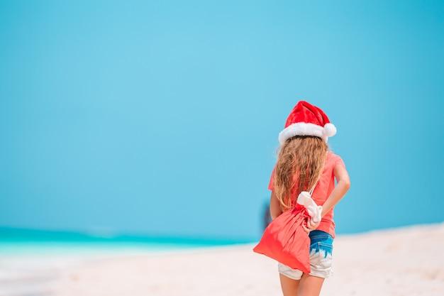 熱帯のビーチのサンタ帽子のかわいい女の子
