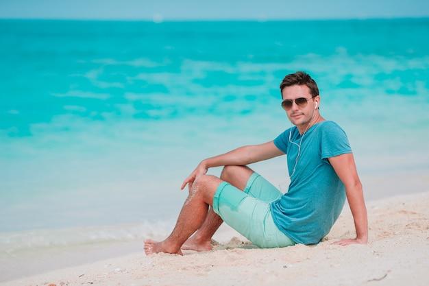 白い熱帯のビーチで若い男