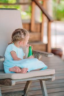 屋外カフェで朝食を食べてのかわいい女の子