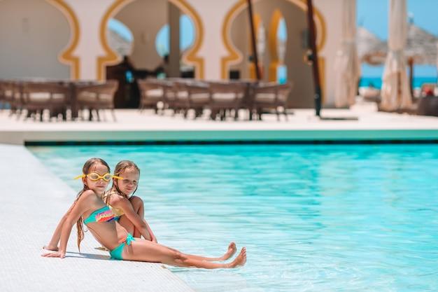 休暇中に屋外スイミングプールで遊ぶ愛らしい女の子
