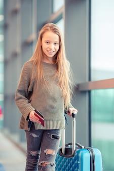 窓の近くの大きな国際空港の空港でのかわいい女の子