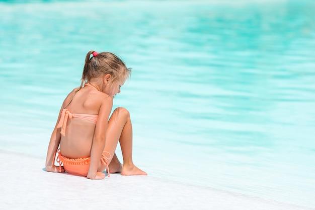 屋外スイミングプールで愛らしい少女