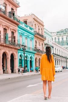 Туристическая девушка в популярном районе в гаване, куба. вид сзади молодой женщины путешественник
