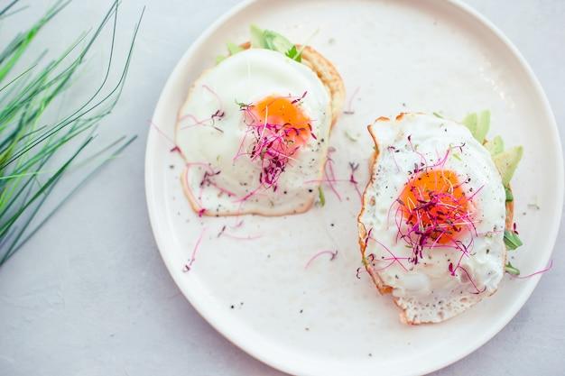 Концепция здорового питания. вкусный бутерброд с авокадо и яичницей