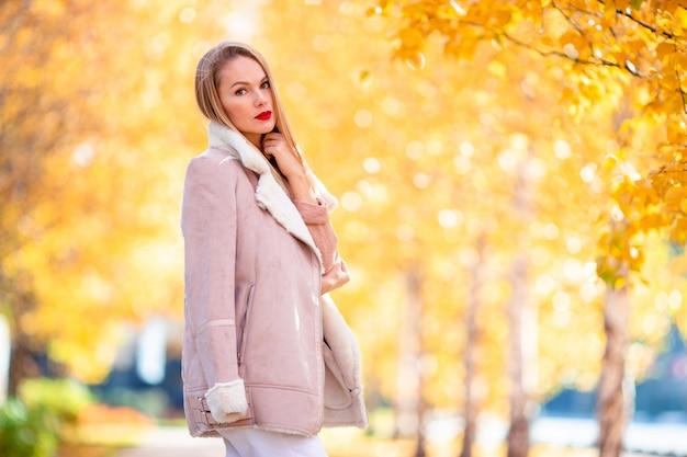 秋のコンセプト - 秋の紅葉の下で秋の公園でコーヒーを飲みながら美しい女性