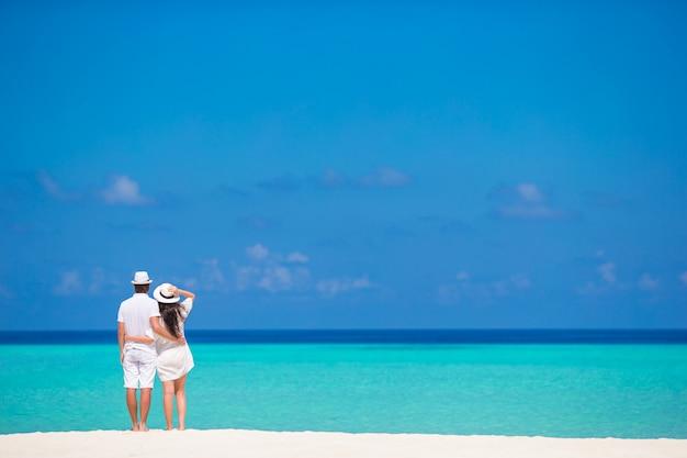 夏休みに白いビーチで若い幸せなカップル