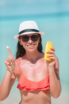若い女性はビーチで彼女の鼻にクリームを適用します。