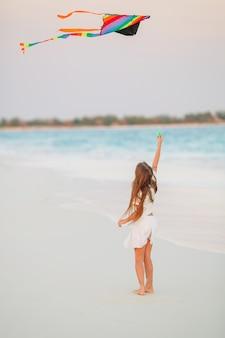 Маленькая девочка летать змей на пляже с бирюзовой водой
