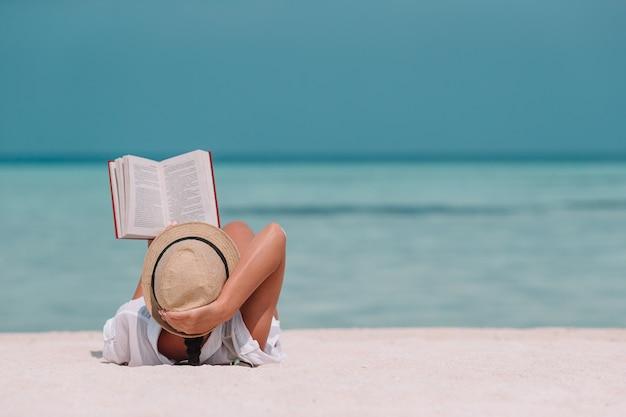 熱帯のモルディブのビーチの間に本を読む若い女性