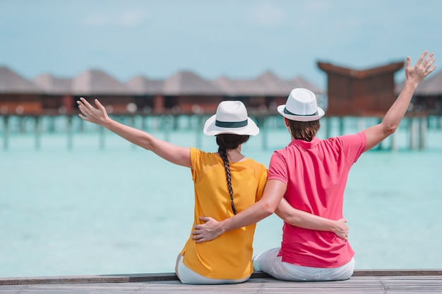新婚旅行で熱帯の島でビーチの桟橋で若いカップル