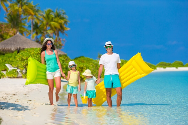 膨脹可能な空気マットレスとおもちゃの白いビーチで幸せな美しい家族