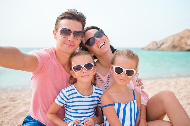 Молодая красивая семья, принимая селфи на пляже