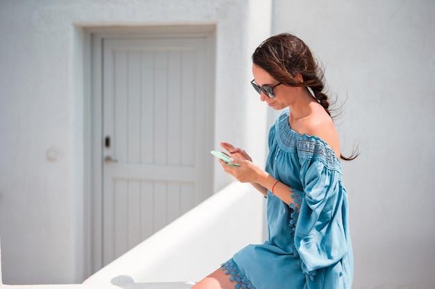 路上で屋外の携帯電話を持つ女性。モバイルスマートフォンを使用しての観光客。
