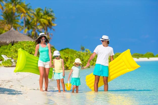 膨脹可能な空気マットレスと白いビーチで幸せな美しい家族