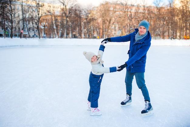 Маленькая девочка учится кататься с отцом на катке на свежем воздухе