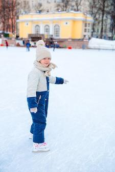 屋外アイススケート場でスケートのかわいい女の子