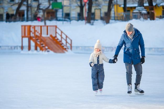 Маленькая прелестная девушка с отцом учится кататься на коньках на катке