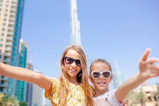 Счастливые девушки гуляют в дубае с небоскребом