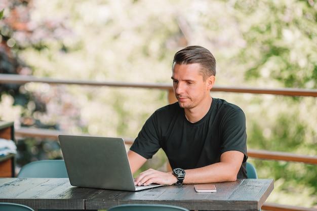 ノートパソコンを持つ若い男が自宅で動作します