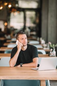 Молодой человек с ноутбуком в открытом кафе, пить кофе.