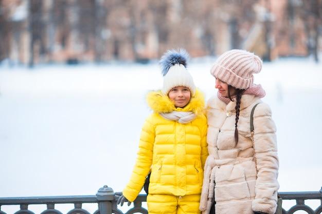 アイススケート場でスケートをする彼女の母親と一緒にかわいい女の子