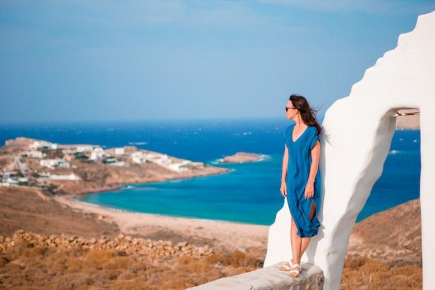 Молодая женщина и традиционная белая церковь с видом на море на острове миконос, греция