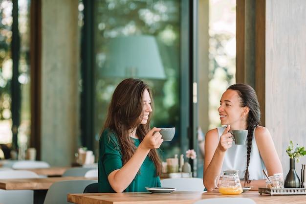 Счастливые усмехаясь молодые женщины с кофейными чашками на кафе. концепция общения и дружбы